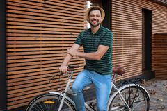 Man with bicycle on street near wall. Man with bicycle on street near wooden wall royalty free stock image