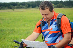 Man with a bicycle and the tourist map Stock Images
