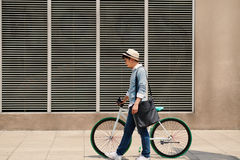 Man with bicycle. Vietnamese guy with bicycle walking along the street Stock Photography