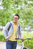 Man with bicycle. Vietnamese young man with bicycle standing outdoors Royalty Free Stock Images
