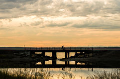 Man bicycling over a railroad trestle on cloudy sunset evening. Royalty Free Stock Image