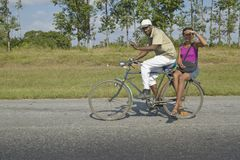 Man bicycling with woman on the back of the bike through the countryside of central Cuba Royalty Free Stock Photos