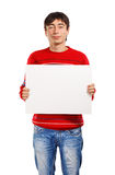 Man with big advertisement. Man in red striped sweater stands on white background holding big business card Royalty Free Stock Image