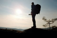 Man with big backpack stand on rock. Sunny spring daybreak Stock Photos