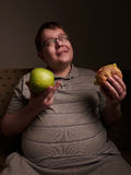 Man with big belly thinking of what to eat - apple or burger. Obesity and gluttony, Royalty Free Stock Photography