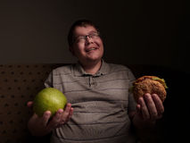 Man with big belly thinking of what to eat - apple or burger. Obesity and gluttony, Stock Photo