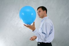 Man with big blue baloon. Man wearing business clothes, standing and holding big blue baloon royalty free stock image