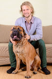 Man with big dog. Young man at home playing with a big bullmastiff dog. positively laugh Royalty Free Stock Photo