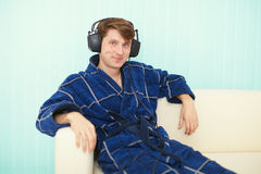 Man in big ear-phones sits on sofa Stock Image