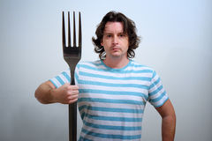 Man with big fork as a Neptune trident Stock Image