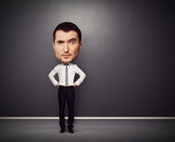 Man with big head. Full-length funny picture of businessman with big head over dark background Royalty Free Stock Image