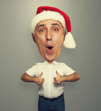 Man with big head showing thumbs up. Amazed xmas man with big head showing thumbs up over grey background stock photography