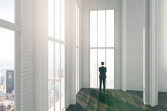 Man in big light loft room with city view and wooden flo Stock Photos