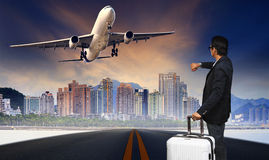 Man with big luggage standing on raod and watching to airplane f Stock Photo