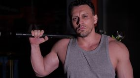 Man with big muscles holds a heavy hammer slung over his broad shoulders. A strong man with big muscles holds a heavy hammer slung over his broad shoulders stock footage