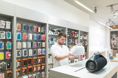 Man with a big music column stands in the technology store in the accessories department royalty free stock photo