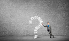 Man and big question mark. Young confident businessman leaning on big question mark Stock Photography