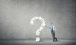 Man and big question mark. Young confident businessman leaning on big question mark Royalty Free Stock Photography