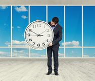 Man with big white clock in empty room Stock Images