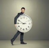 Man with big white clock going forward Stock Photos