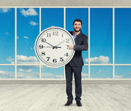 Man with big white clock standing Stock Images