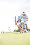 Man bijwonende vrouw die bal plaatsen op golfcursus tegen hemel Royalty-vrije Stock Afbeelding