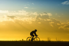 Man on a bike. Silhouette Stock Images