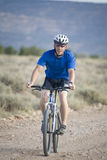 Man on bike front viewf. A man riding a bike on dirt road Royalty Free Stock Photos