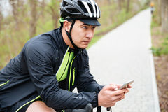 Man in bike helmet with bicycle using cell phone Royalty Free Stock Image