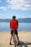 Man with bike on a mountain lake Royalty Free Stock Images