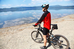 Man with bike on a mountain lake Royalty Free Stock Image
