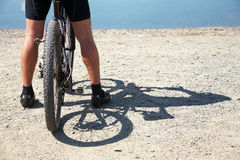 Man with bike on a mountain lake Stock Photography