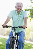 Man on bike outdoors smiling. At camera royalty free stock images