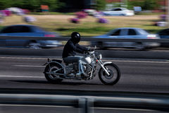 The man on the bike rides around town. The bike rides through the city at high speed. White motorcycle with chrome pipes. Man in jeans and a black helmet Stock Photos