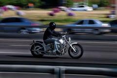 The man on the bike rides around town. Stock Photos