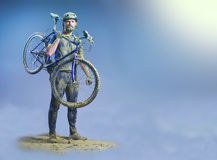 The man with bike in sand standing on abstract background. Collage stock photos