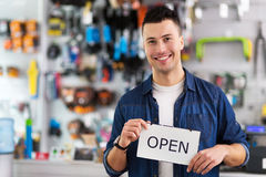 Man in bike shop holding open sign Stock Photos