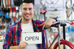 Man in bike shop holding open sign Royalty Free Stock Photos