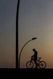A man on a bike. A silhouette of a man on a bike Stock Photography