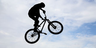 Man with a bike. Silhouette of a man doing an jump with a bike Royalty Free Stock Image