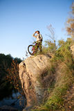 Man with the bike standing. Autumn nature. Man with the bike standing on a rock. Autumn nature Stock Photo