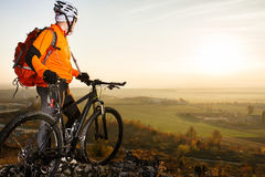 Man with the bike standing on a rock. spring nature Royalty Free Stock Image