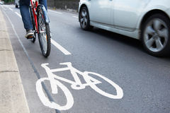 Man On Bike Using Cycle Lane As Traffic Speeds Past stock image