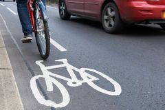 Man On Bike Using Cycle Lane As Traffic Speeds Past Stock Photo