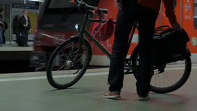 Man with bike waiting for subway train. Man parking his bicycle on the platform of underground station and waiting for the next train stock video footage