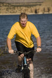 Man on bike in water. A man on his bike going through deep water showing the expression of surprise and fun Stock Images