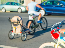 Man on bike. Young caucasian man riding on bike with hooked baby carriage Stock Images