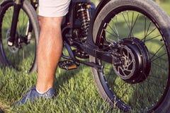 Man biker sitting on electric bike. Ebike bicycle environmentally friendly eco e-mountainbike transport. Healthy lifestyle stock photo