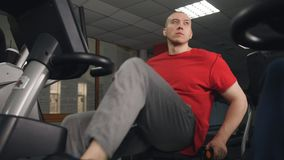 Man biking in the gym, exercising his legs doing cardio training cycling bike. Portrait of happy man on exercise bike. Fit man working out on exercise bike at stock video footage