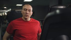 Man biking in the gym, exercising his legs doing cardio training cycling bike. Portrait of happy man on exercise bike. Fit man working out on exercise bike at stock footage